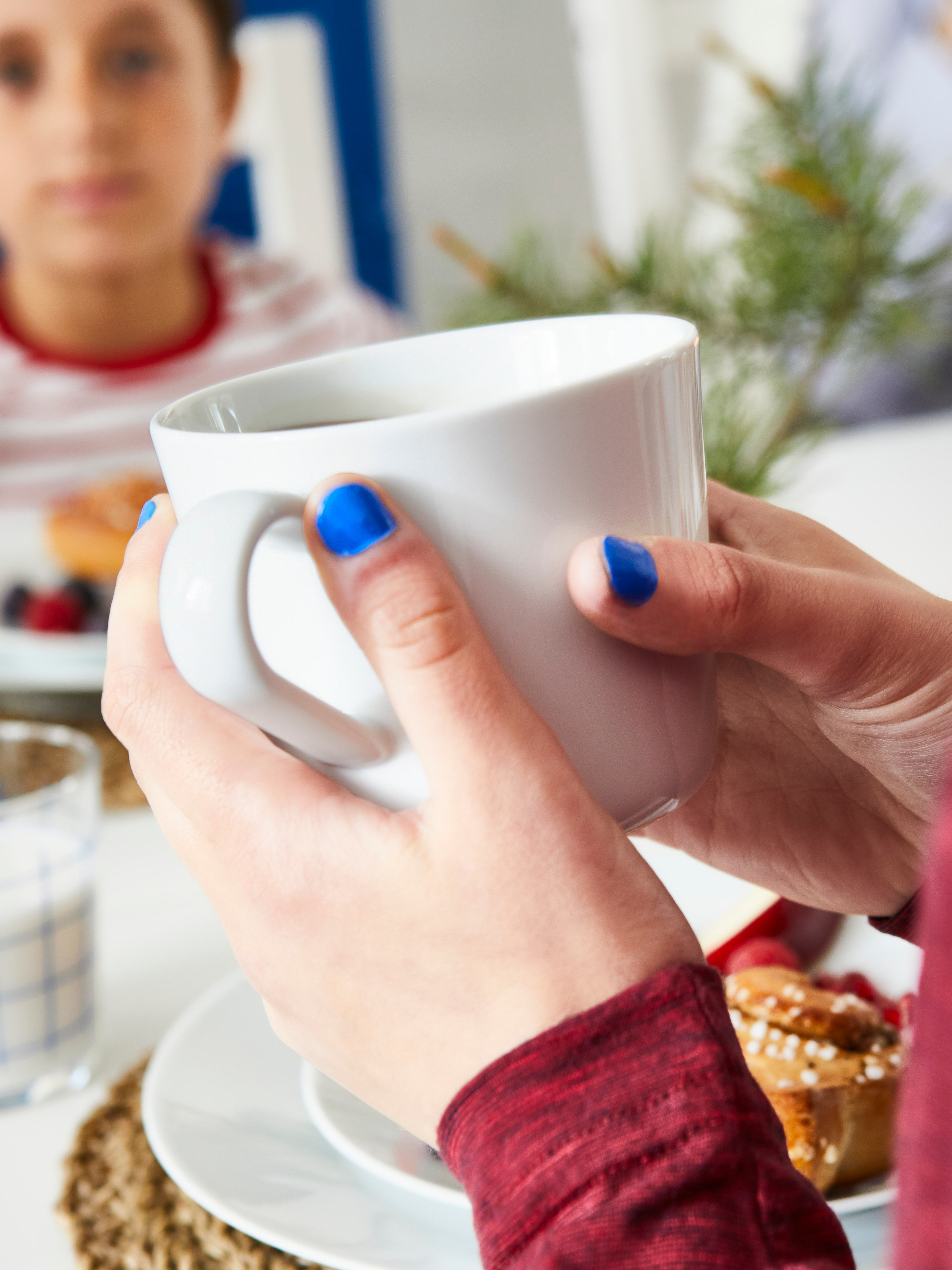 Close-up of an IKEA 365+ mug being held in a woman's hands with cool blue nail polish, with a small boy in background.