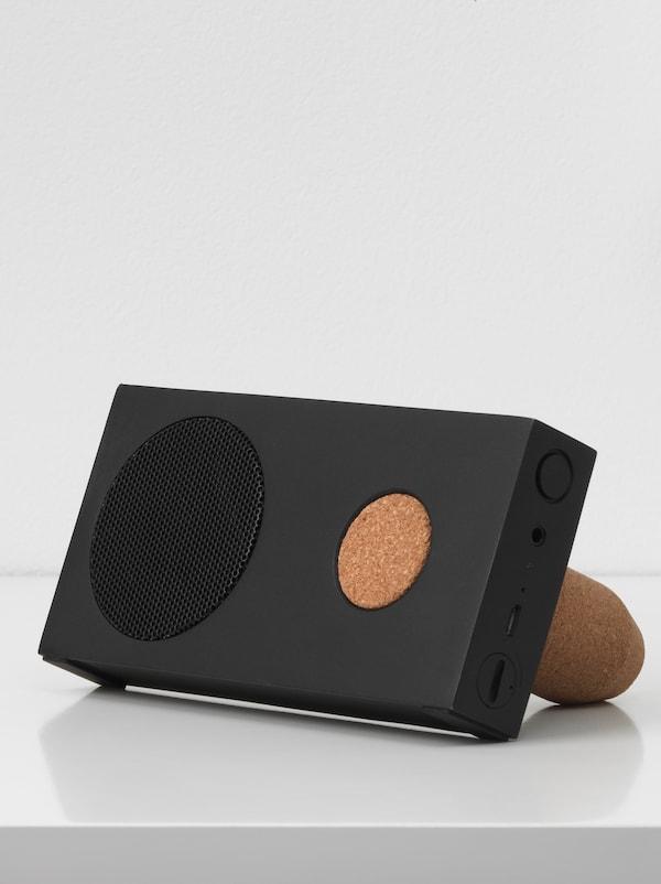 Ein schwarzer tragbarer ENEBY Bluetooth-Lautsprecher mit einem Halter aus Kork steht auf einer weißen Oberfläche vor einer weißen Wand.