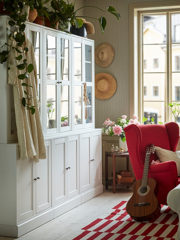 Mobile bianco con ante a vetro con sopra delle piante, in un soggiorno rosso e bianco.