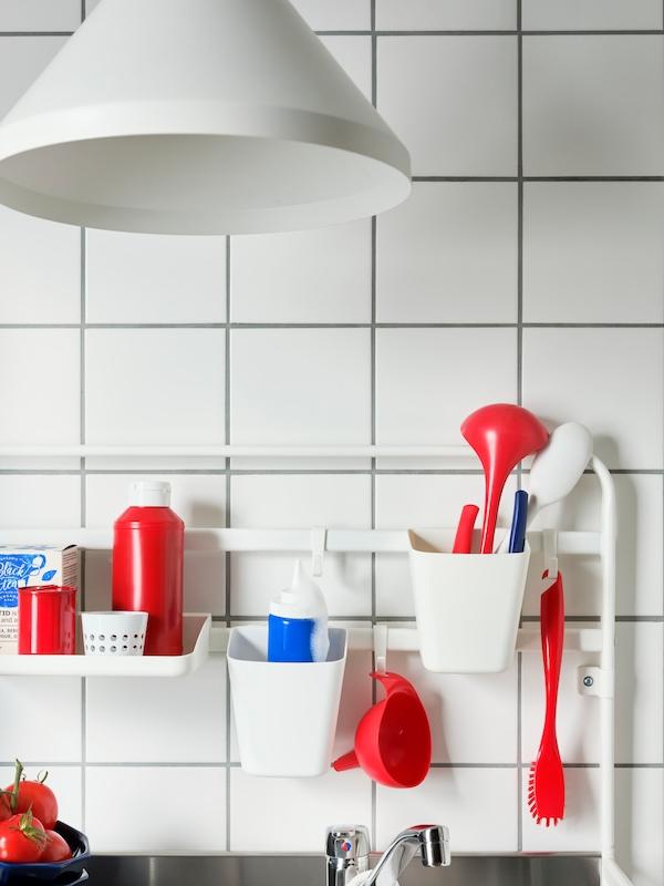 Białe haczyki SUNNERSTA, pojemniki i półka z czerwonymi, niebieskimi i białymi przyborami kuchennymi zawieszone na szynie minikuchni SUNNERSTA.