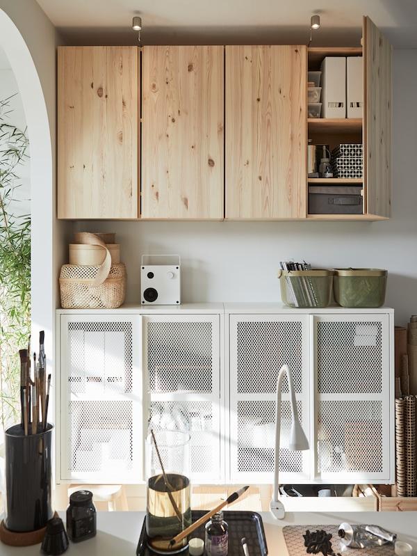 På väggen sitter två förvaringsskåp i trä, under dem finns två vita förvaringsskåp. Ovanpå står en högtalare och korgar.