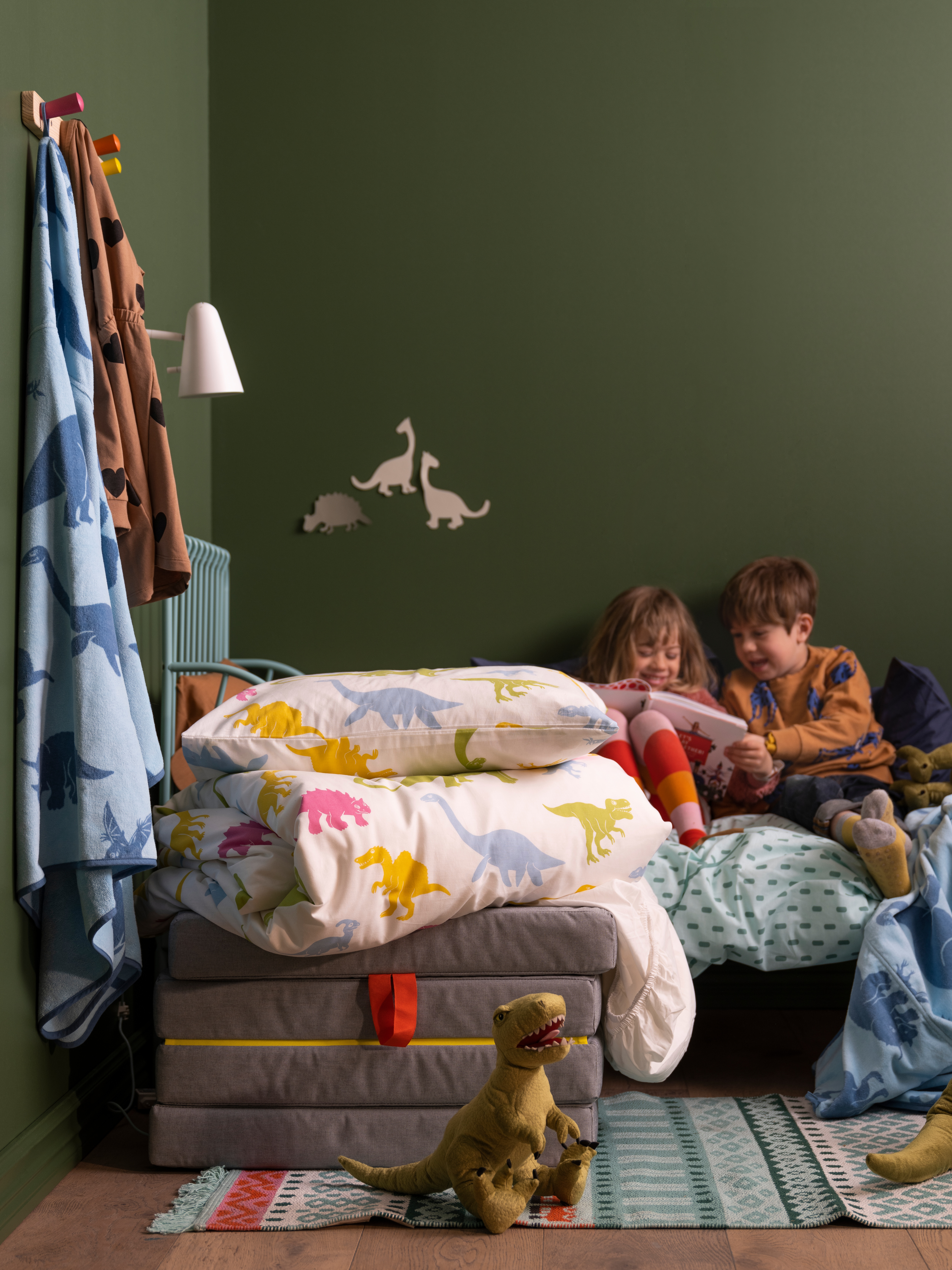 JÄTTELIK dinosaur-themed bed linen on bed, wall and floor next to two soft toy dinosaurs with two children in bed reading.