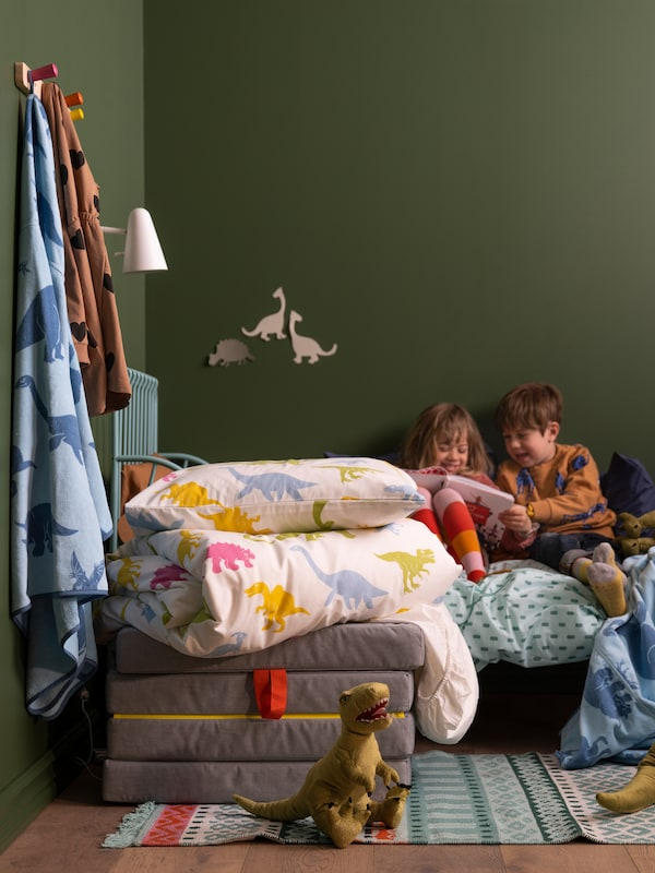 Two children read a book in a bed dressed with assorted bedlinens, behind a colourful dinosaur duvet cover and pillow.