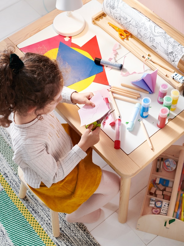 A child seated at a table, doing crafts.