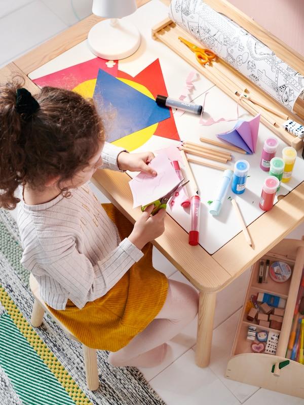Lapsi istuu FLISAT-lastenpöydän äärellä ja askartelee värikkäillä papereilla.