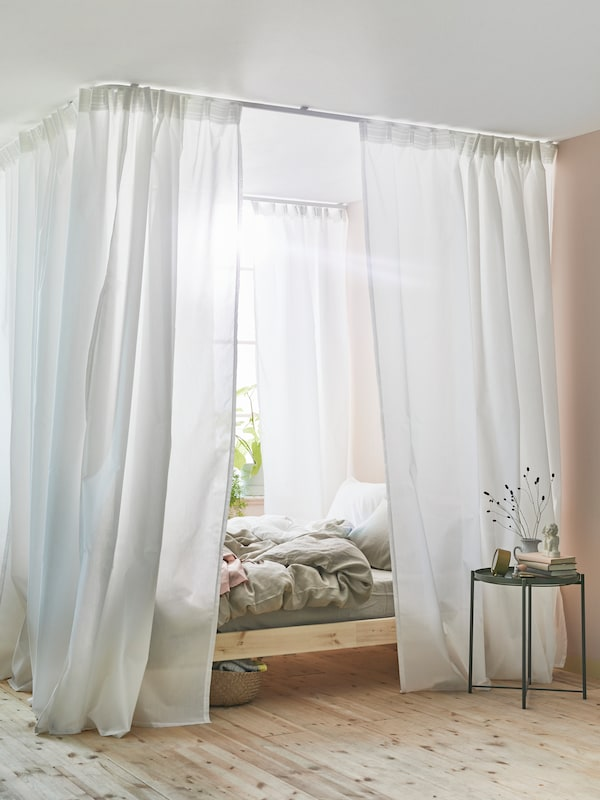 HILJA curtains surrounding a bed in a well-lit room. A plant on a GLADOM table.