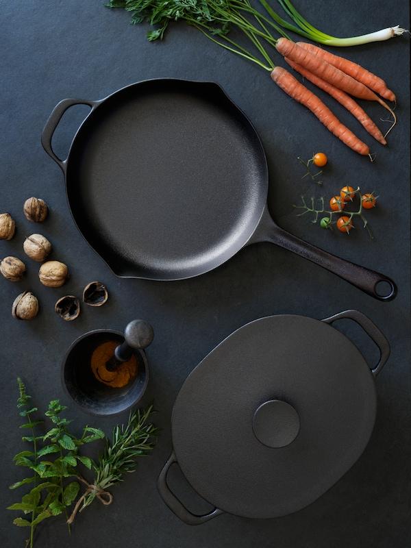 قدرة ومقلاة VARDAGEN على طاولة خشبية سوداء محاطة بمكونات الطهي مثل الجزر والمكسرات.