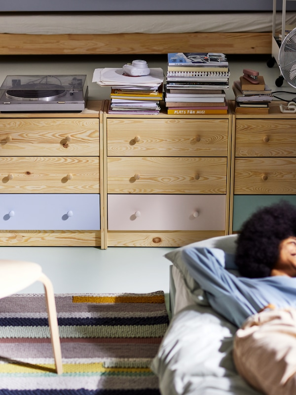 Three pine RAST chests of drawers with the bottom drawers painted in different colours, beside a woman lying on a bed.