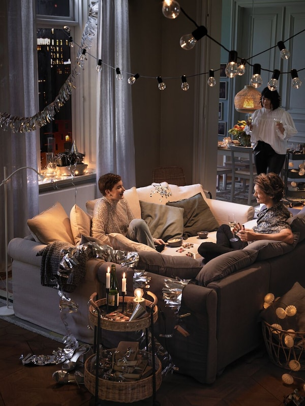Two people sitting facing each other in facing sofas, one standing, side tables with candles, lighting and decoration.