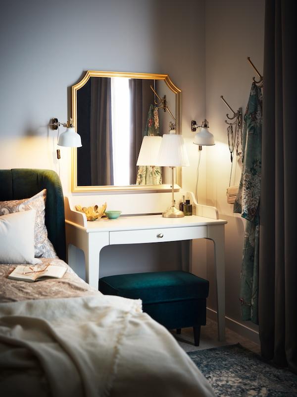 A light beige LOMMARP desk stands in a corner under a SVANSELE mirror beside a dark green TUFJORD upholstered bed.