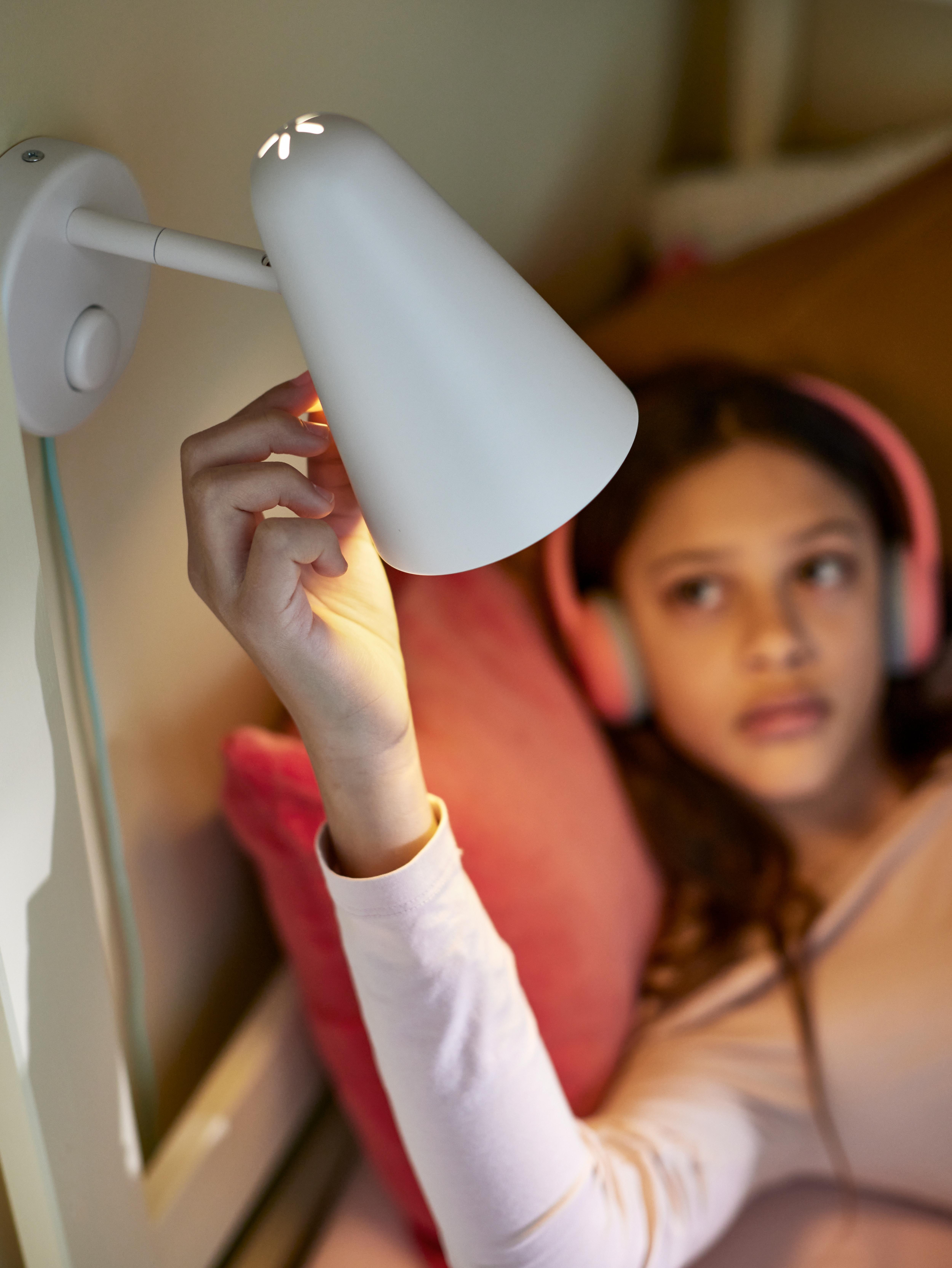 Entzungailu arrosak dituen neska bat kuxin arrosaren gainean etzanda FUBBLA LED hormako lanpara zuriaren ilunpea jartzen.