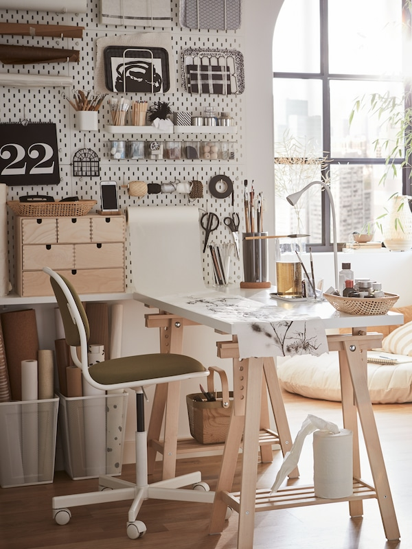 A SKÅDIS white pegboard with accessories containing various items on a wall above a LAGKAPTEN/MITTBACK desk in white/birch.