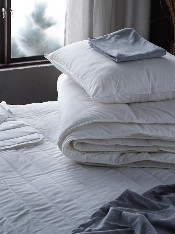 كيس وسادة مطوي على وسادة موضوعة فوق لحاف SMÅSPORRE مطوي على سرير بالقرب من النافذة.