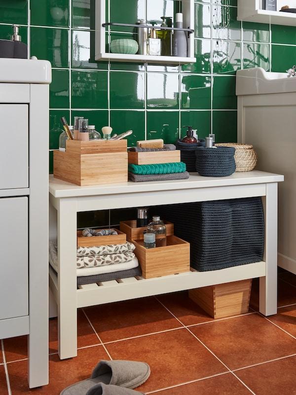 Un banc HEMNES est placé entre deux lavabos dans une salle de bains carrelée verte. Boîtes et serviettes rangées sur les étagères.