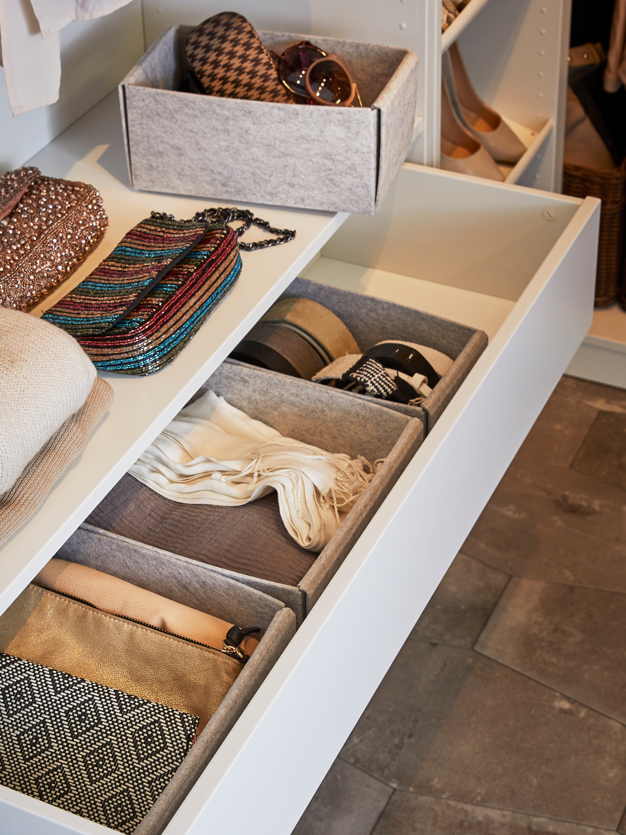 The bottom of a wardrobe interior has an open drawer with a row of light grey KOMPLEMENT boxes holding groups of accessories.