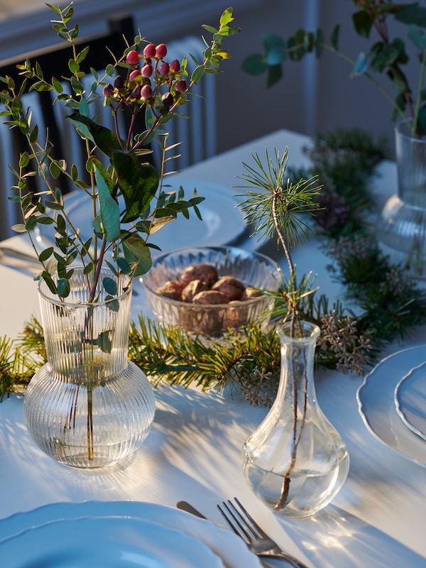 مزهريات VILJESTARK و PÅDRAG الزجاجية الشفافة بها أغصان رفيعة، موضوعة جنبًا إلى جنب على طاولة ثابتة مزينة باللونين الأبيض والأخضر.