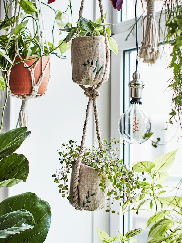 Handmade jute planters with embroidered details hanging at different heights in a window inside a home.