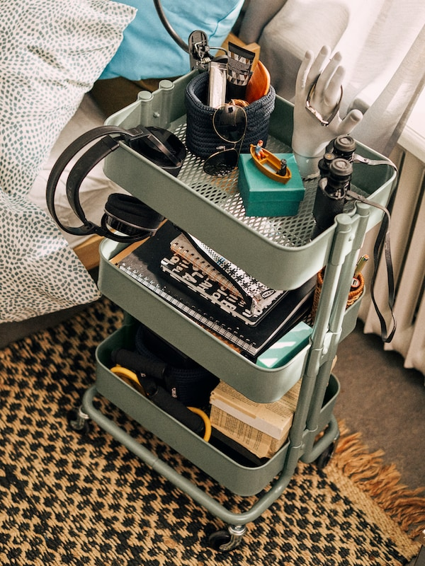 A gray-green RÅSKOG trolley standing on a mat next to a bed. The trolley is filled with notebooks and other things.