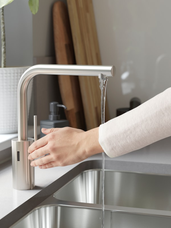 A person with a white top activates the IKEA TÄMNAREN motion sensor stainless steel sink tap, turning on the water.