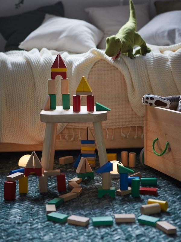 Mehrfarbige Teile aus dem UNDERHÅLLA Holzbauklötzeset stehen verbaut auf dem Fußboden eines Kinderzimmers.