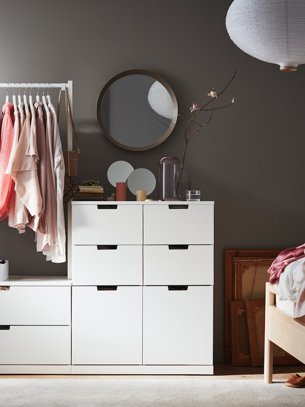 Cómoda NORDLI de 8 cajones contra una pared bajo un espejo LANGESUND y con una barra con ropa colgada.
