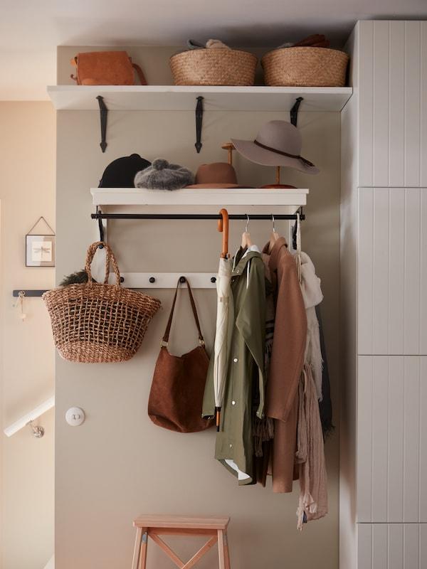 Eteinen jossa on seinällä valkoinen HEMNES-naulakki jossa roikkuu takkeja ja laukkuja. Naulakon alla on puinen BEKVÄM-porrasjakkara.