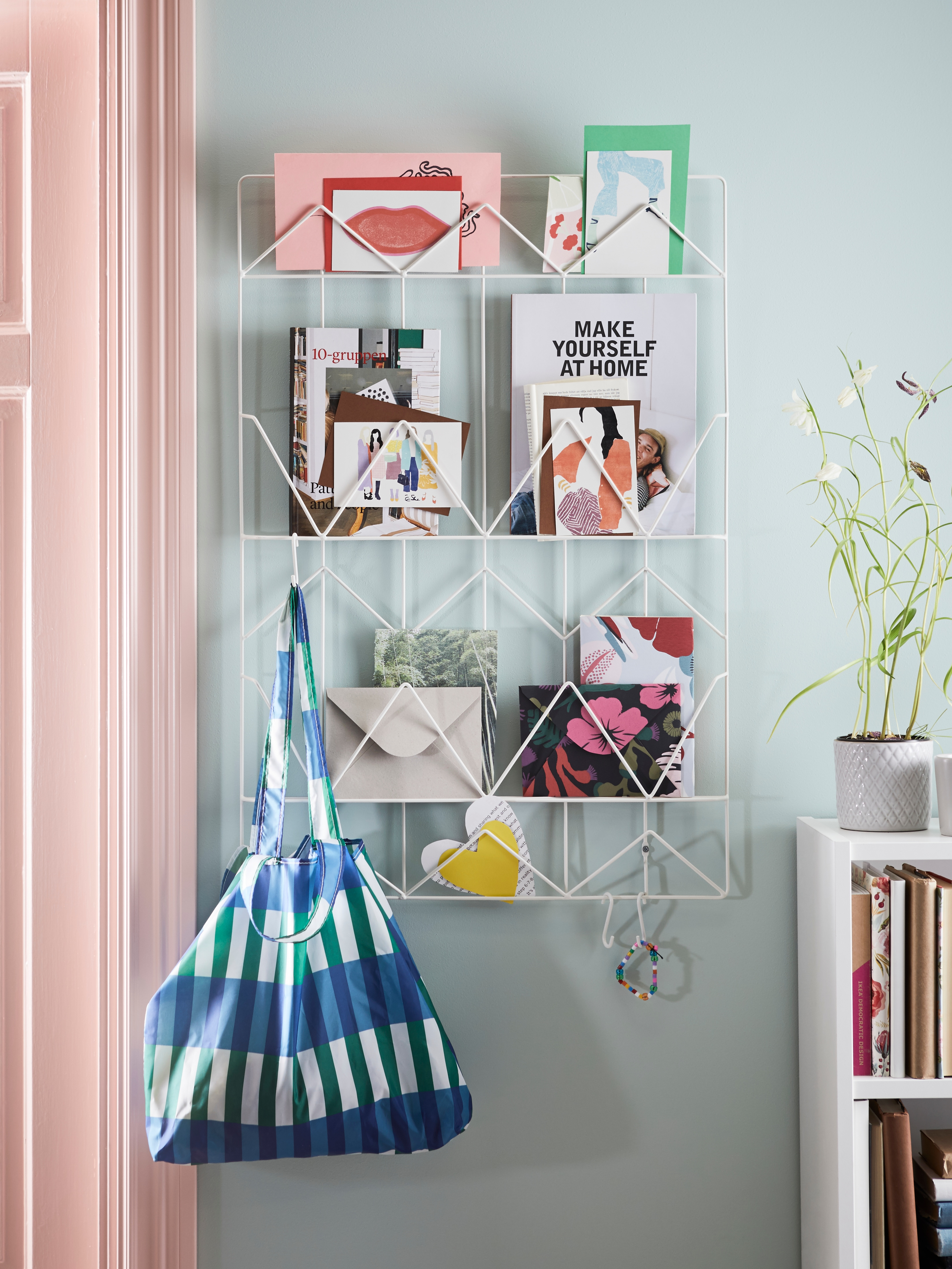 White steel KVICKSUND memo board with books and cards and a bag hanging on it, next to a bookshelf with a plant on top.
