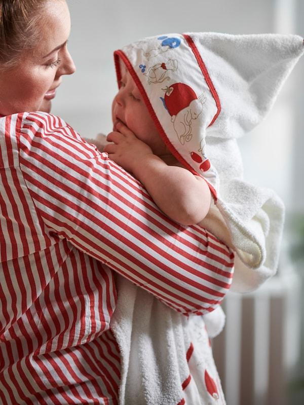 Una donna con una camicia a righe bianche e rosse tiene in braccio un bambino che indossa un accappatoio con cappuccio RÖDHAKE.