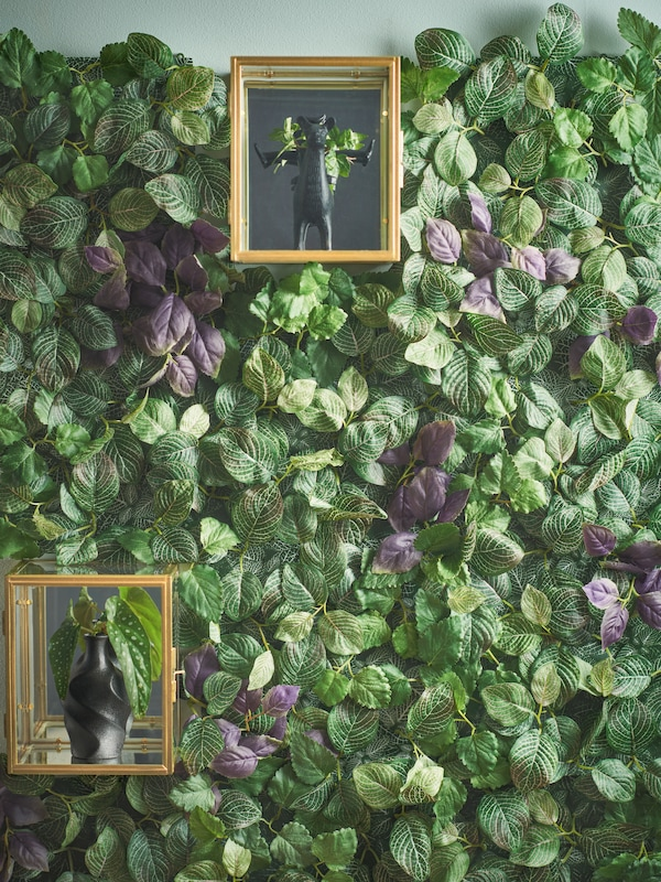 A wall of artificial green leaves with two smaller glass display cases holding decorative plant pots.