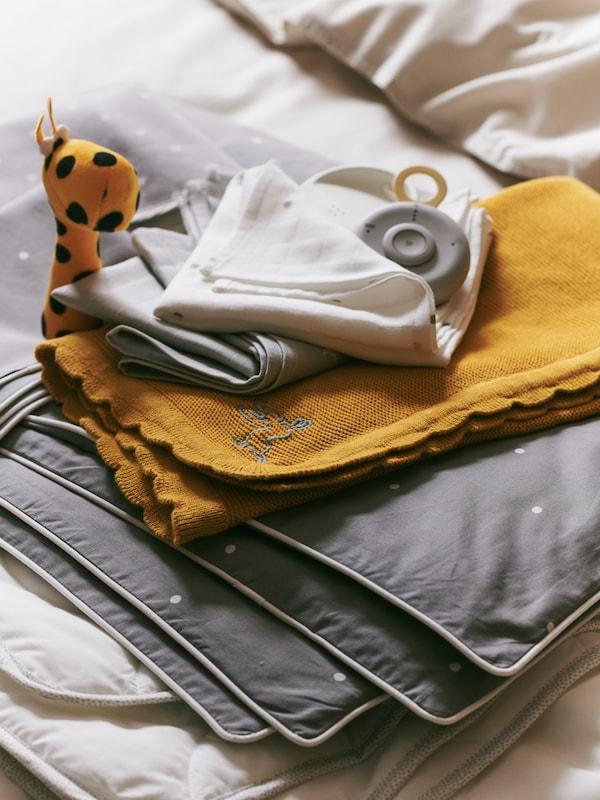 الوحدة الأم لجهاز مراقبة الأطفال UNDVIKA موضوعة على كومة من منتجات المنسوجاتبما في ذلك بطانية SOLGUL صفراء داكنة.
