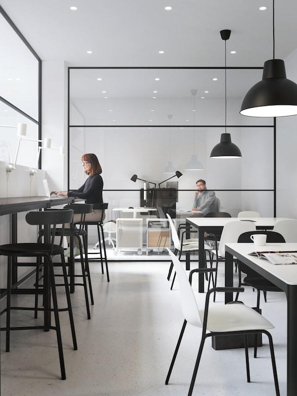 Kaksi työskentelyaluetta, toinen baatyylinen korkeine jakkaroineen ja toinen pitkä rivi pöytiä. Taka-alalla mies työskentelemässä lasiseinäisessä työhuoneessa.