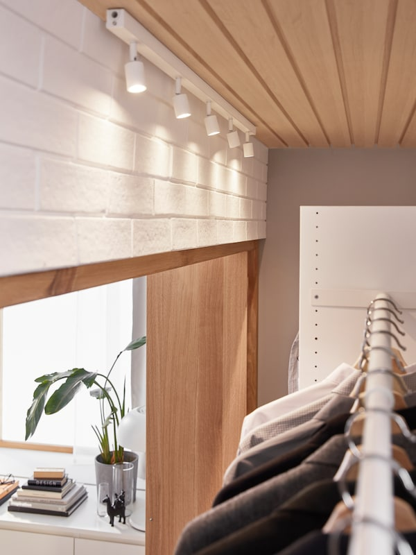 A white BÄVE LED ceiling track with adjustable spotlights shines on the clothes hanging inside a fitted AURDAL wardrobe.
