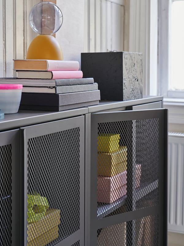 Närbild på byrå med IVAR dörrar i grått mesh där det står böcker och annan dekoration ovanpå