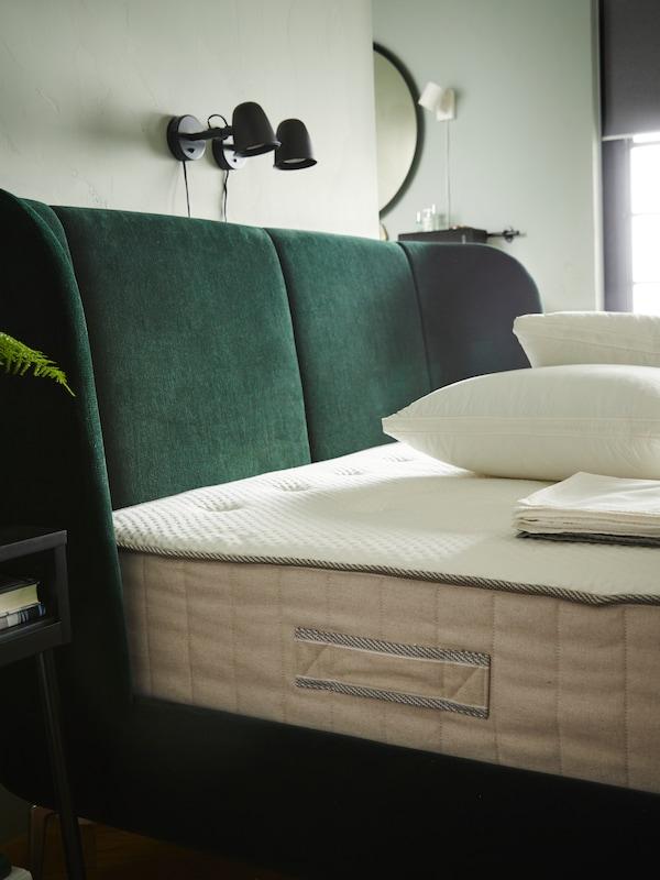 Eine VATNESTRÖM Matratze auf einem grünen TUFJORD Bettgestell, darüber sind zwei SKURUP Wandleuchten zu sehen. Auf dem Bett liegen Kissen und gefaltete Bettwäsche.