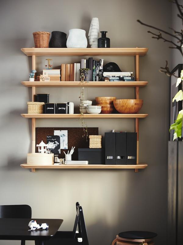 Kulhot, aikakauslehdet, astiat ja kirjat varastoitu viilusta valmistettuun seinähyllyyn, taustalla harmaa seinä.