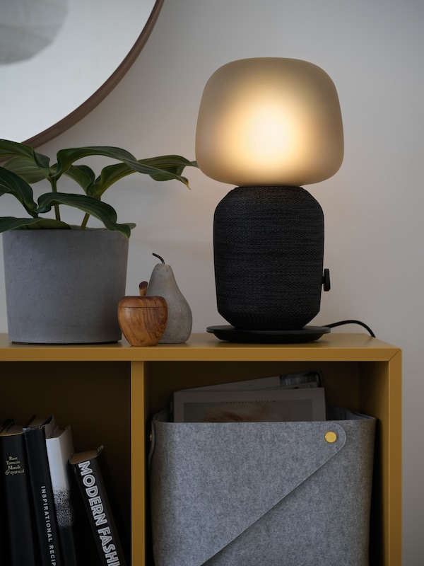 A black SYMFONISK table lamp with WiFi speaker, next to a houseplant and ornaments, on top of EKET storage cabinets.