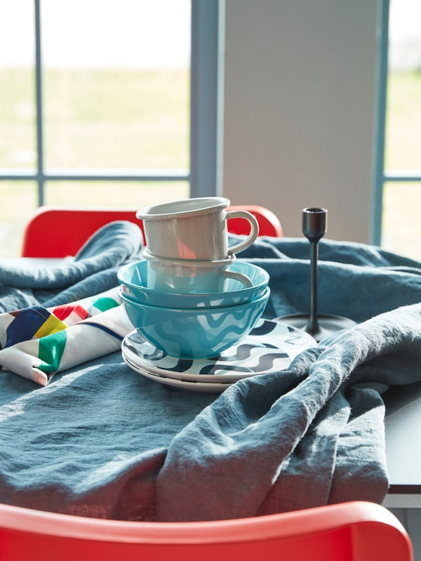 A breakfast table setting for two with a table cloth, mugs, tableware and turquoise FÄRGRIK bowls.