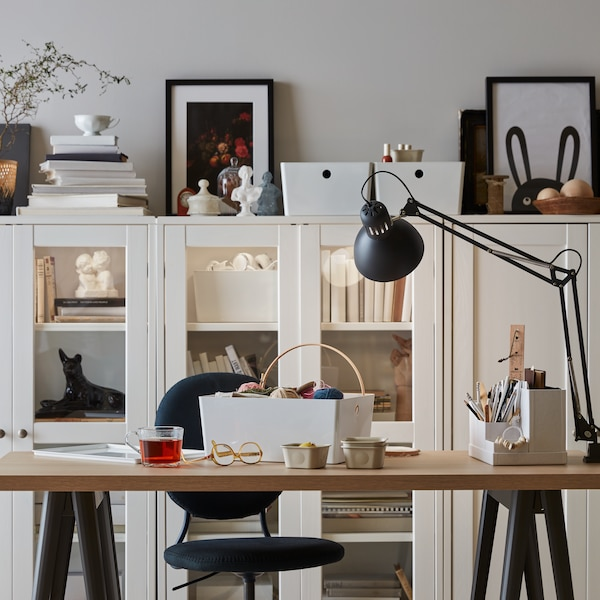 An adaptable workspace with a large wooden desk, black table lamp, and grey chair, placed in front of white display cabinets.