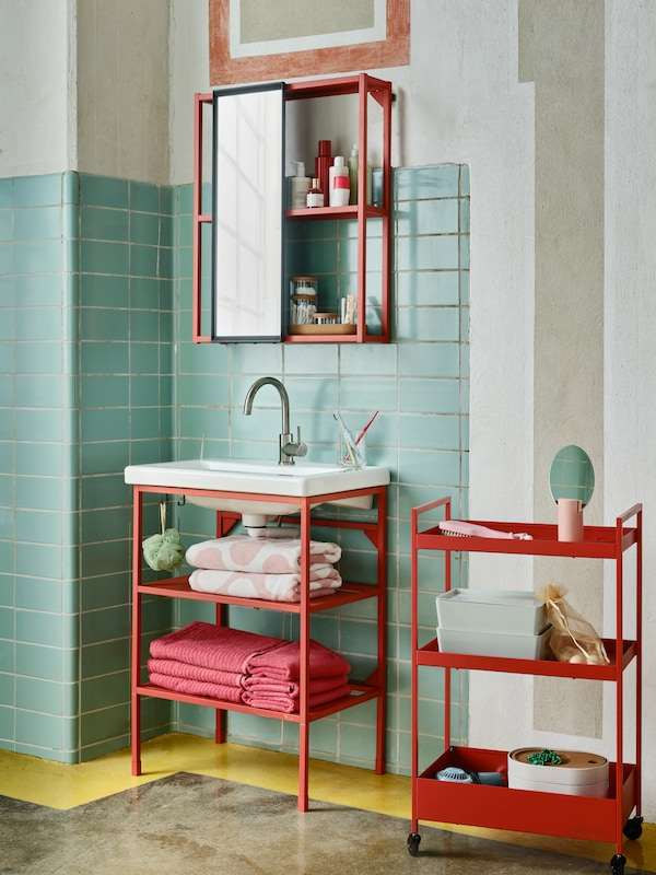 An ENHET washbasin stand and overhead storage in red-orange with an anthracite/grey mirror in a colourful bathroom.