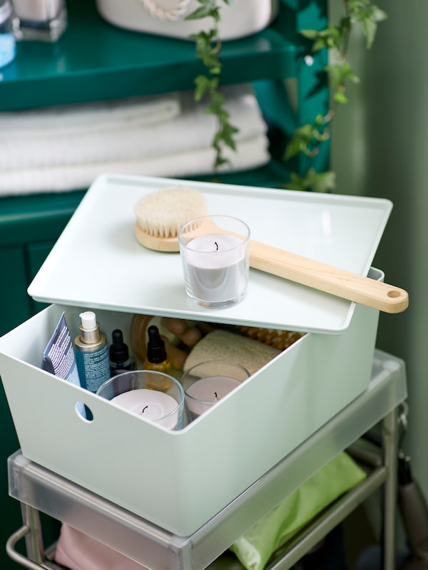 A white KUGGIS box with its lid slightly open containing various bathroom items. A candle and a bathroom brush stand on top.