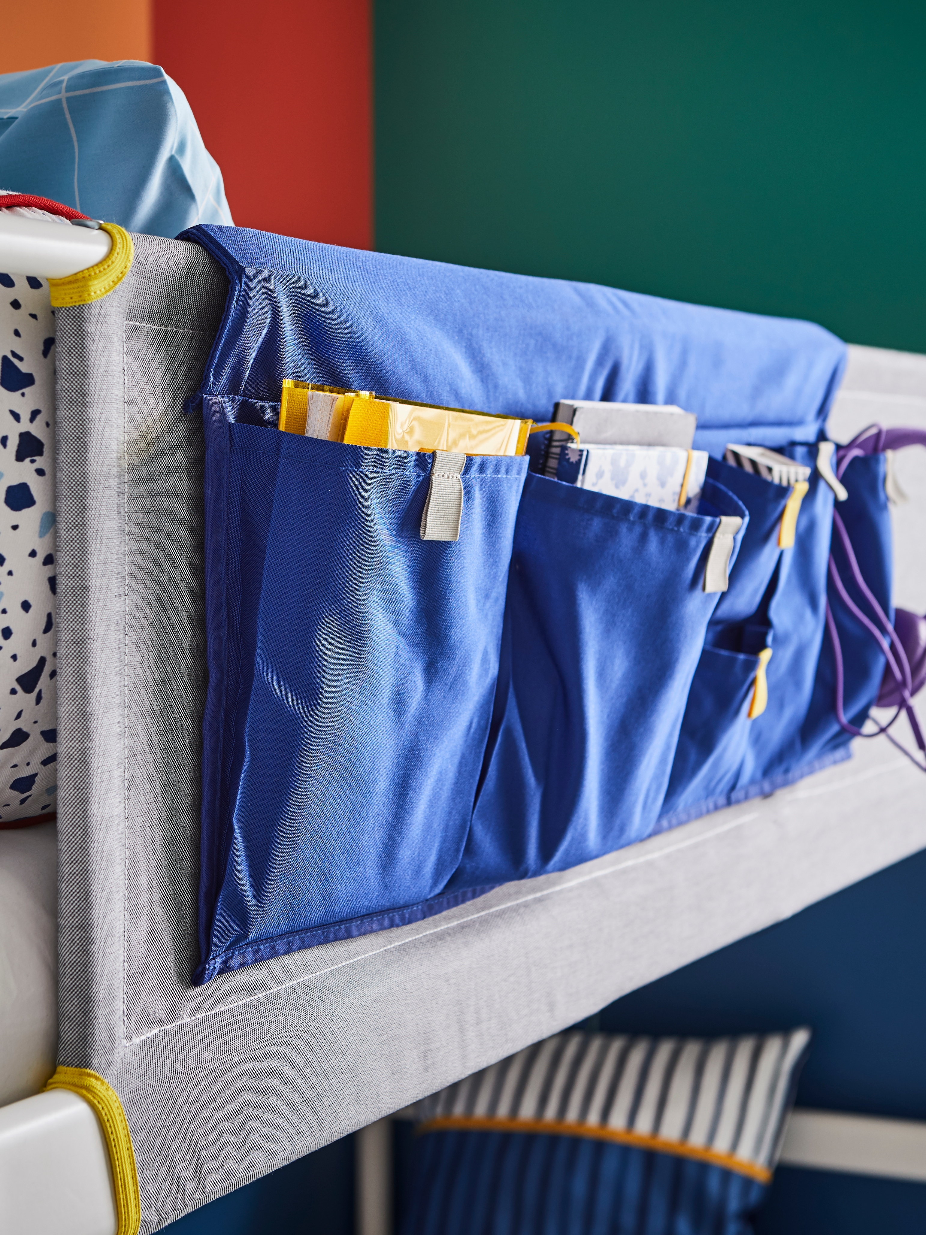 Plavi MÖJLIGHET džep za krevet s džepovima različitih veličina u kojem su knjige koje se nalaze na zaštitnoj ogradi kreveta na kat.