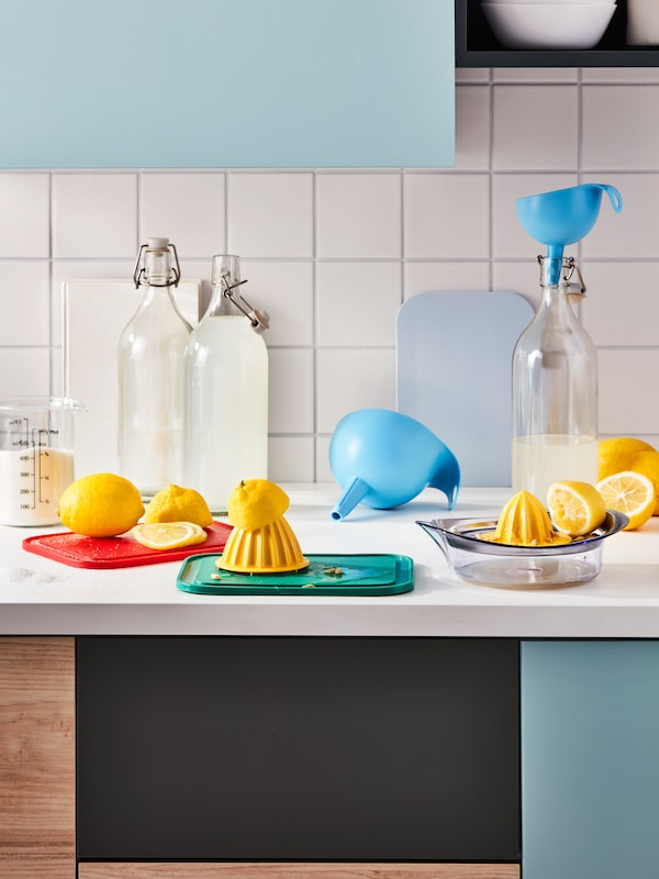 A kitchen worktop in the middle of a lemonade-making session; lemons, a SPRITTA squeezer, CHOSIGT funnels and KORKEN bottles.