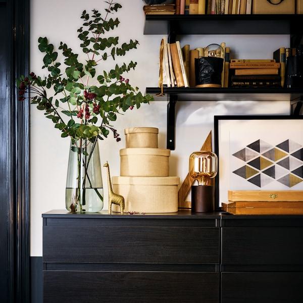 Zwei KULLEN Kommoden mit fünf Schubladen, auf denen Dekogegenstände arrangiert sind. An der Wand darüber sind dunkle Wandregale zu sehen.