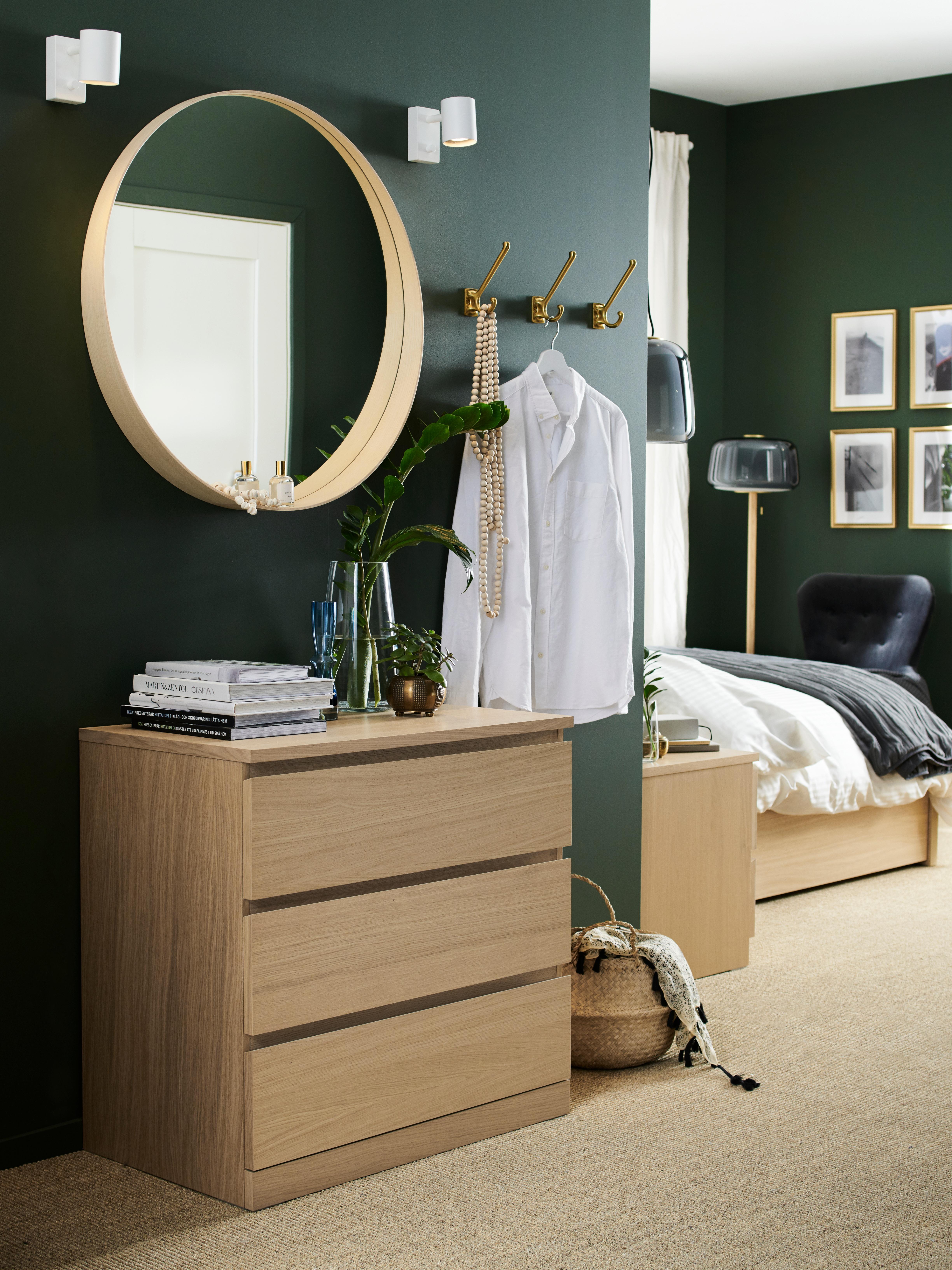 Un angolo per prepararsi al mattino all'interno di una camera da letto, con cassettiera con tre cassetti MALM in impiallacciatura di rovere con mordente bianco, specchio rotondo e ganci attaccapanni a parete.