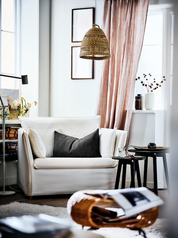 A BACKSÄLEN armchair in the corner of a bright living room with a pendant lamp overhead and a coffee table nest beside it.