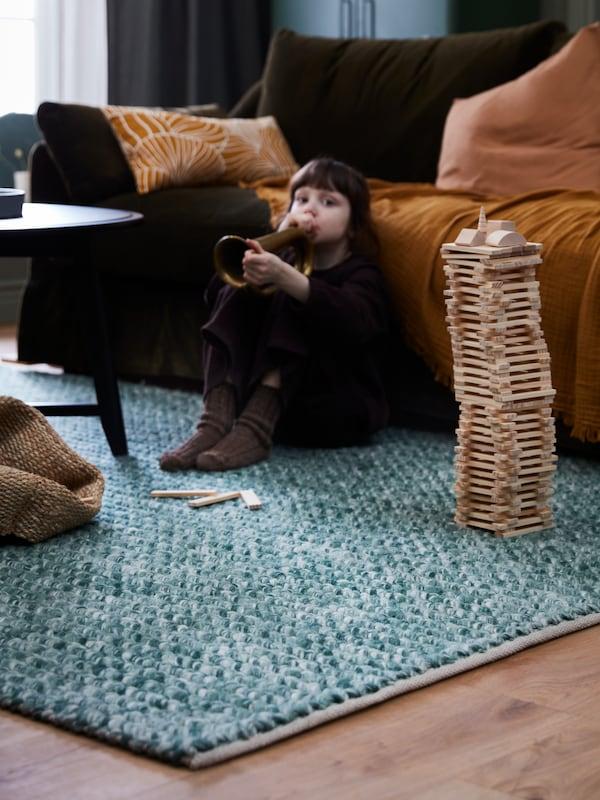 Une petite fille joue avec un clairon jouet assise sur un tapis de laine AVSKILDRA vert foncé, le dos appuyé contre un canapé FÄRLÖV.