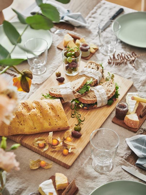 Деревянная сервировочная доска с бутербродами и багетом в окружении посуды нейтральных оттенков