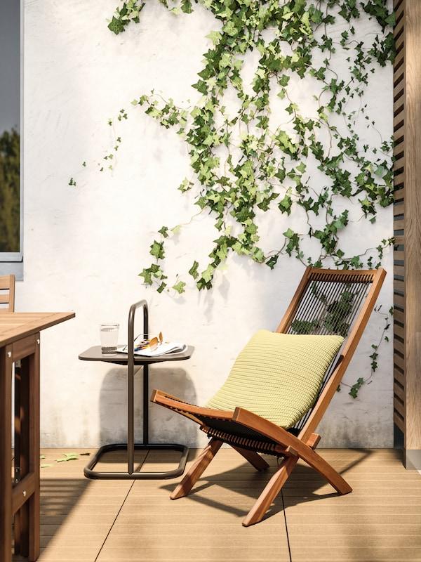 Ein grünes Polster auf einem Liegestuhl aus Holz mit schwarzem Gewebe auf einer sonnigen Terrasse mit Efeu an der Wand. Daneben ein Ablagetisch.