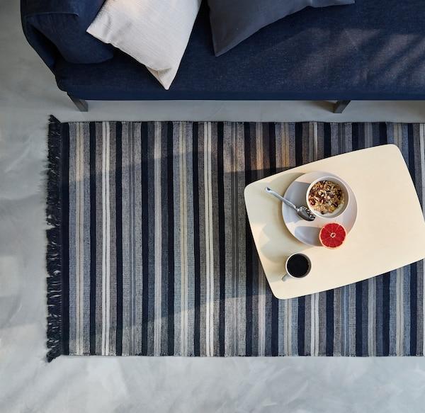 Tabuleiro RÅVAROR em bétula, sobre um tapete de tecido RÅVAROR azul escuro.