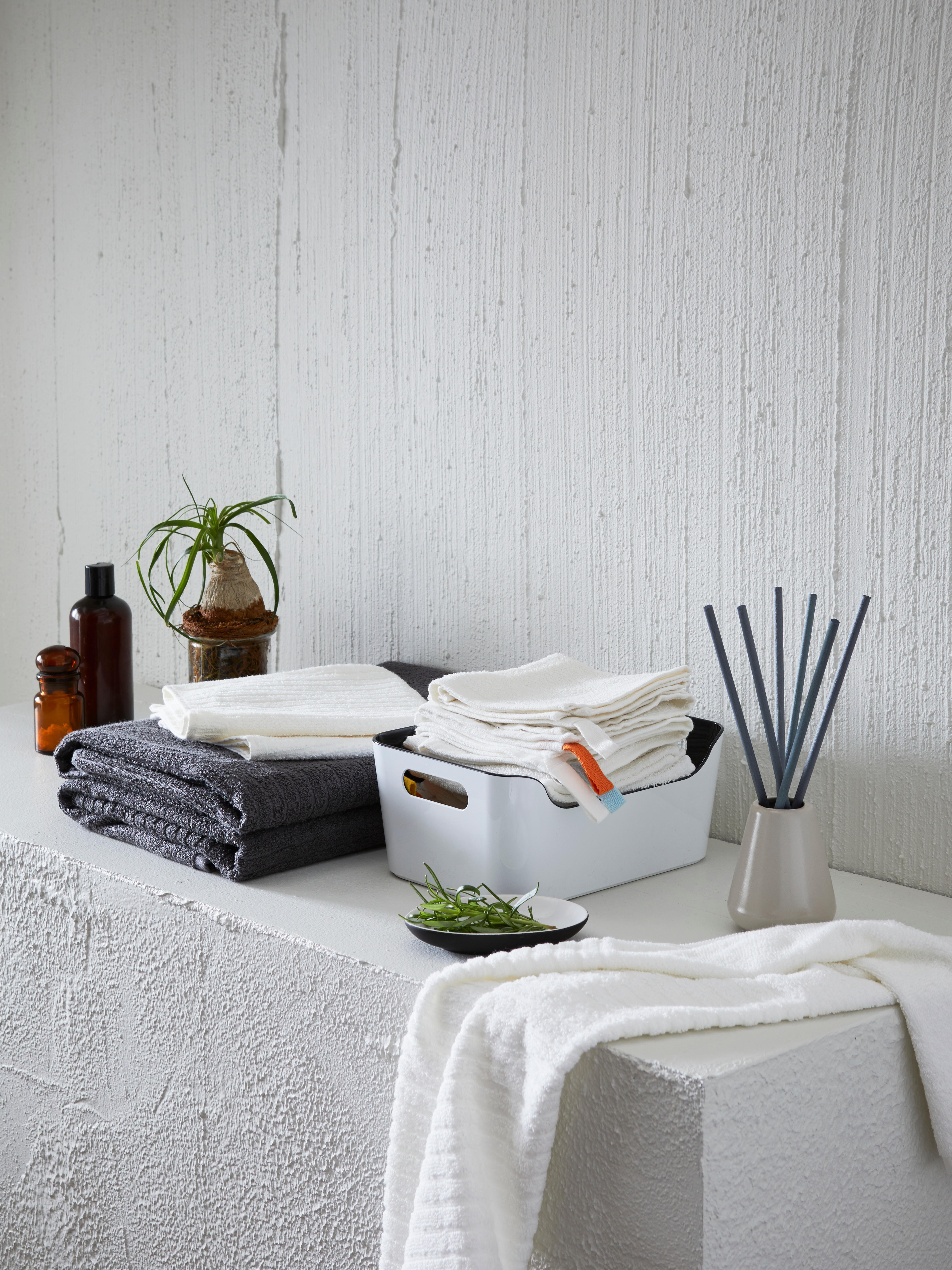 VÅGSJÖN bath towels piled on a shelf next to a box of flannels, a dish of rosemary, bottles, a plant and incense sticks.